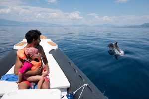 kid and parent doing dolphin spotting at Corinthian gulf with boat trips organised by Lido Hotel